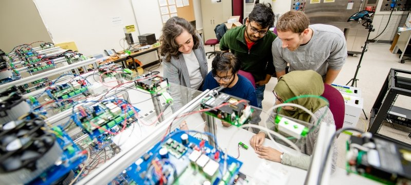 Researchers in the battery lab looking over a battery.
