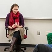 A woman sitting in front of a college class.