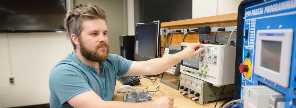 Student operates an oscilloscope and programmable logic controller.