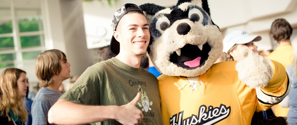Student with Blizzard T. Husky with thumbs up