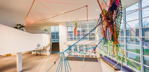 An art installation made of fiber and stretches in the ceiling area, as viewed looking towards campus
