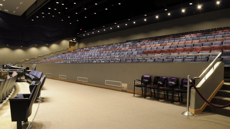Inside the performance hall showing the view of the middle aisle with usher seating and
