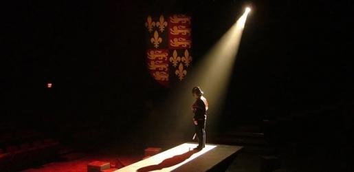 A performer on stage with a coat of arms handing standing in a single spotlight