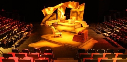 Inside the McArdle Theatre during a dressed set with a golden light shining on the set
