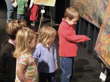 Three K-2 students looking at art in a gallery