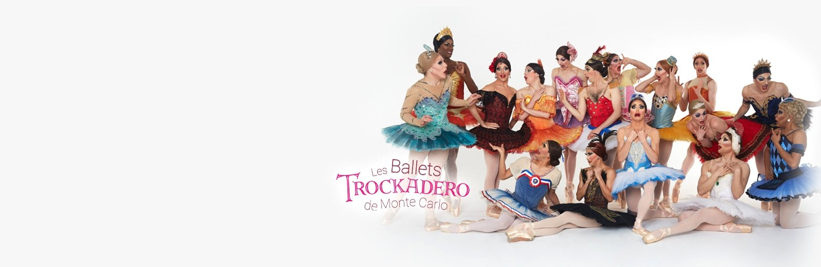 Cast of Les Ballets Trockadero de Monte Carlo in colorful ballet costumes posing with shocked expressions.