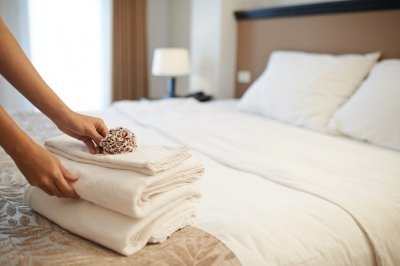 A flower being placed on top of a stack of towels on a hotel bed.