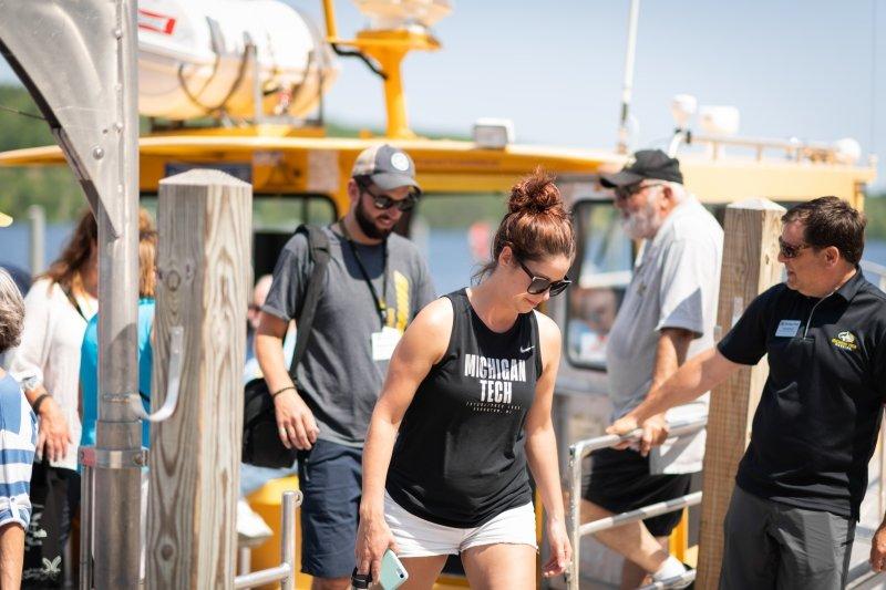 Alumni stepping off Aggasiz boat