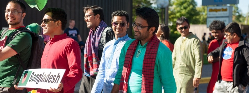 Bangladesh students walking in the Parade of Nations; some are wearing traditional dress and one student is holding a sign that has their country name and flag.