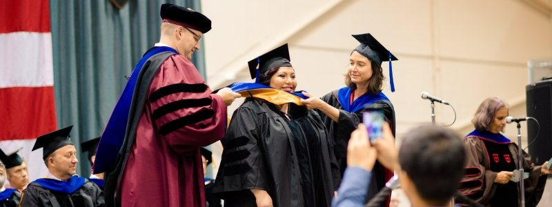 Dean Hemmer and faculty place hood on graduate student at commencement.
