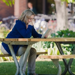 Woman sitting at a picnic table reading on a tablet