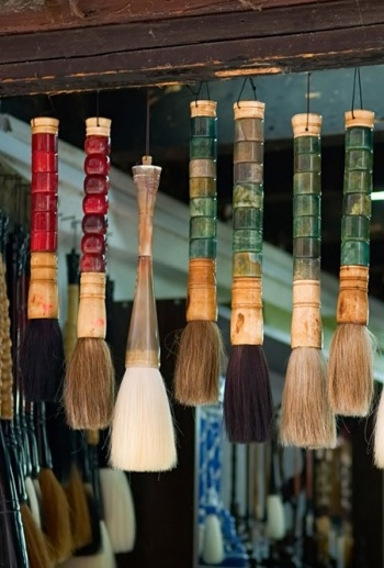 Colorful array of hanging paint brushes.