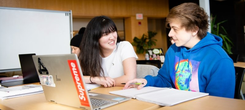 Two students talking in front of laptops