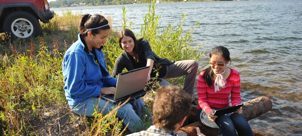 Faculty and students sit on the edge of the Keweenaw Waterway while looking at laptops discussing.