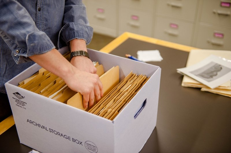 Researcher going through box of large envelopes