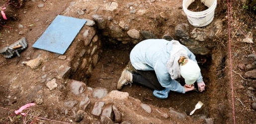 Student inside an excavation square section collecting artifacts