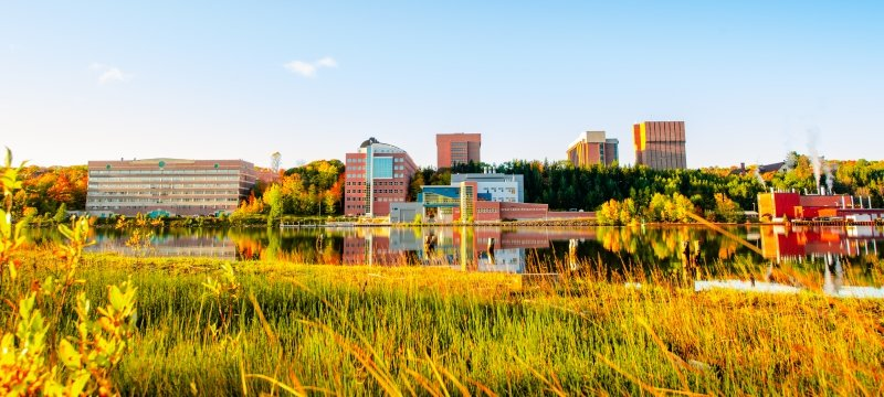 A view of campus from across the waterway in the fall.