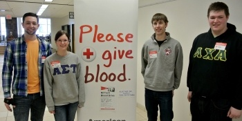 Blood drive students stand by floor poster
