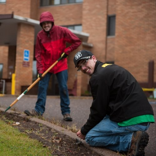 Two Michigan Tech students planting spring bulbs