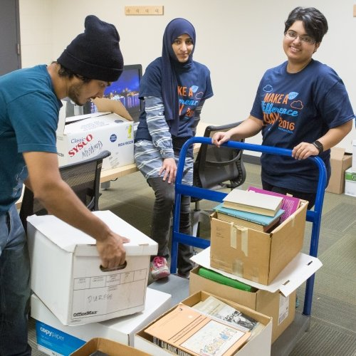 Three Michigan Tech students sorting books in the library