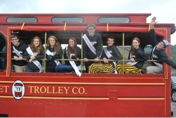 Homecoming court in a red trolley.