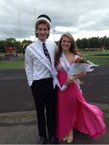 Homecoming king and queen dressed up at the football field.