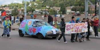 Indian students walking in the parade next to a decorated car.