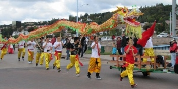 Students carrying a dragon in the parade.