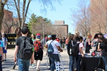 Students at a table and walking through campus.
