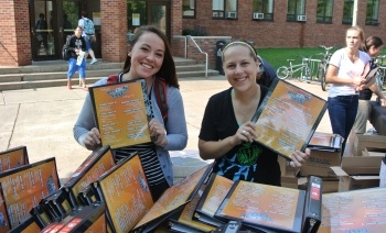 Students in front of the MUB showing off the binders being handed out during Welcome Week.