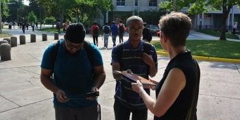 Dean of Students handing out binders to students in the circle drive by the MUB.