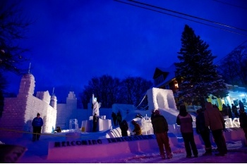 Night view of people looking at a completed snow statue.