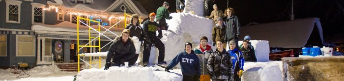 students posing with snow statue