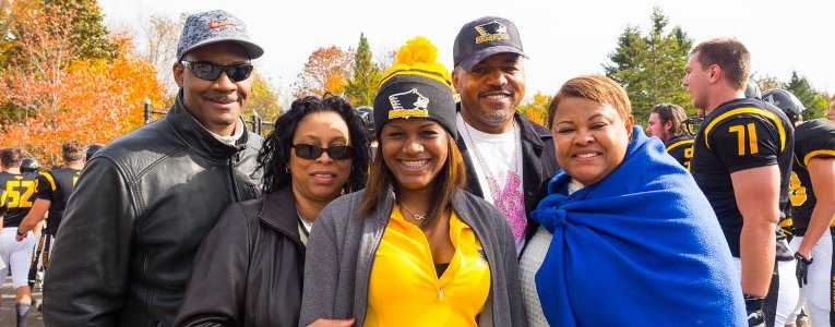 A student and her family pose for the camera at a Michigan Tech football game