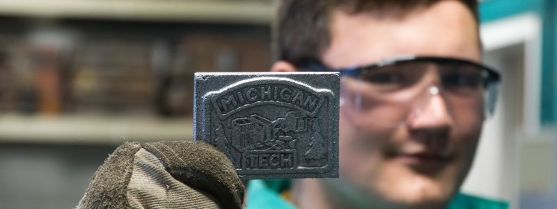 "A man holds up a metal casting that reads ""Michigan Tech."""