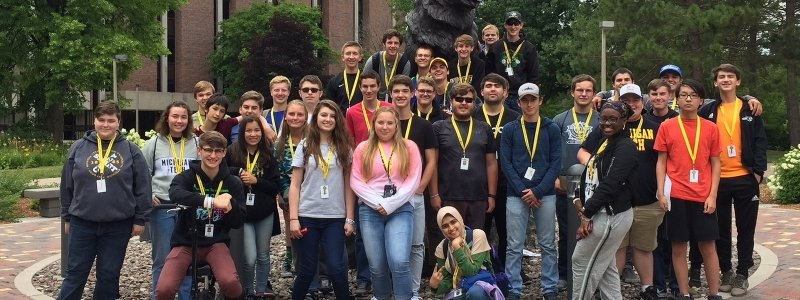 An SYP group photo in front of the Husky statue on Michigan Tech's campus.