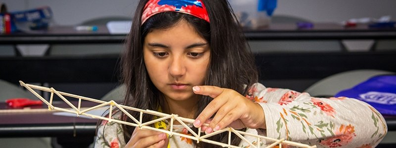 A girl builds a bridge out of balsa wood strips.