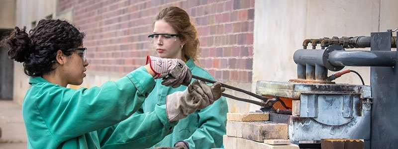 Two young women in safety gear melt metal in a small foundry.