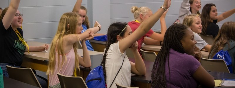 A classroom of young women with their hands raised.