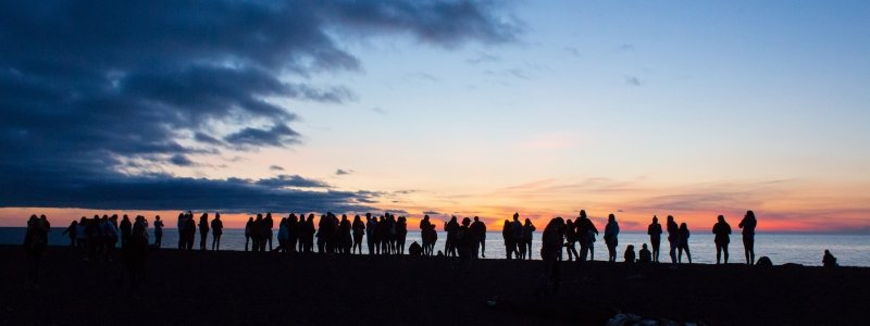 Silhouettes of SYP students watching a sunset on the beach.