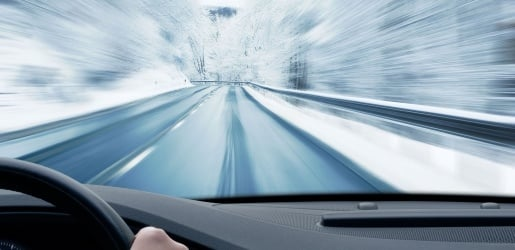 Photo of a vehicle driving during a winter day, with the sides blurbed out to simulate speed.