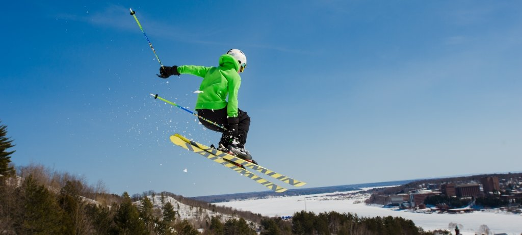 Skier in air with the Michigan Tech campus in the background.