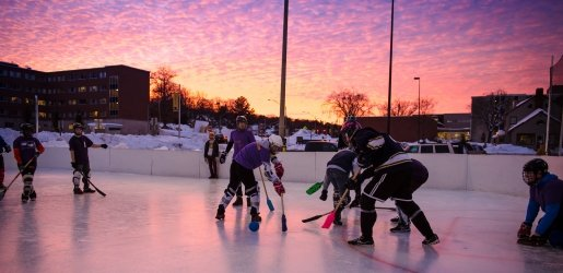 Students playing broomball with a sunset in the background.