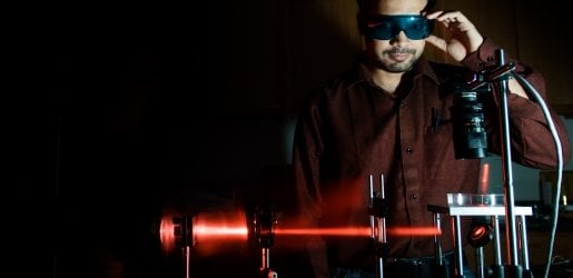 Student looking at a equipment that is shining a laser beam.