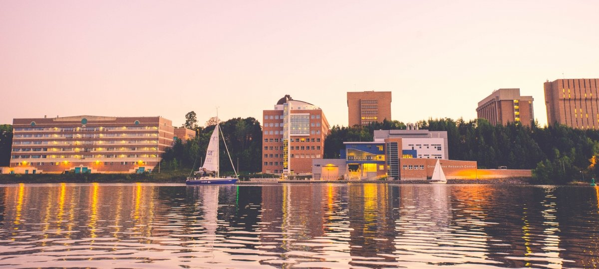 A view of campus from across the waterway with sailboats.