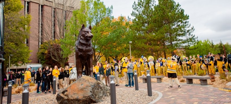 The pep band, Blizzard T. Husky, and other people gathered around the Husky Statue.