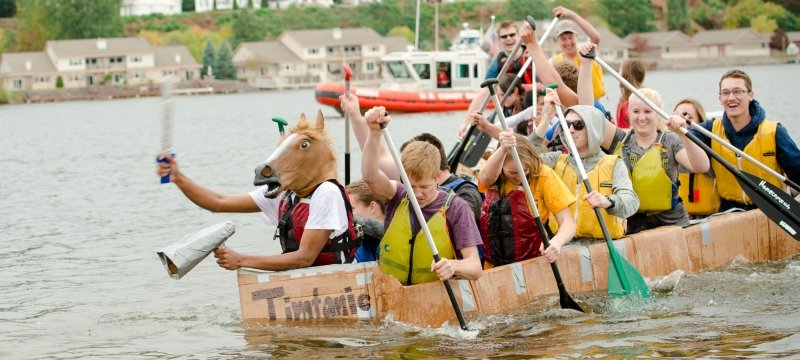 Students in a cardboard boat on the water.