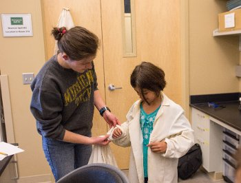 Cat Vendlinski gets help rolling up her sleeves to get ready for a lab lesson.
