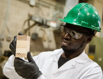 Munkaila Musah holds up a block of cross-laminated timber.