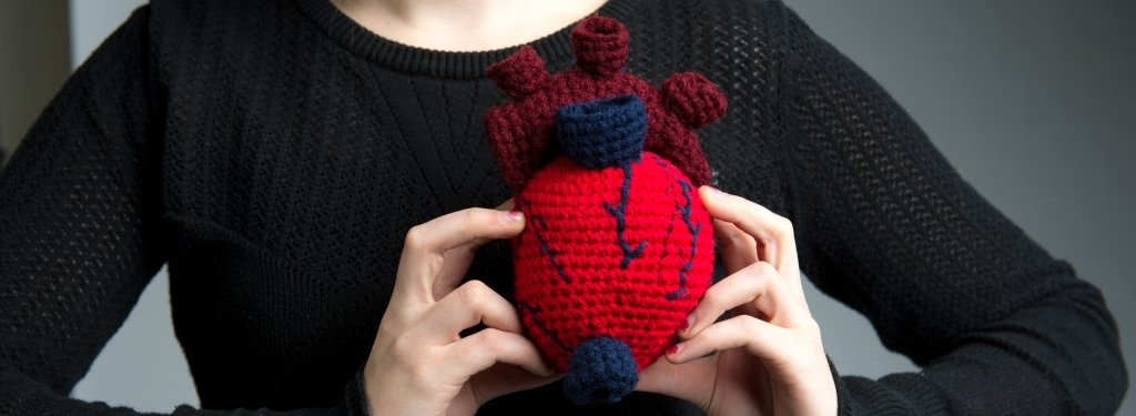 close-up of a young woman holding a crocheted heart